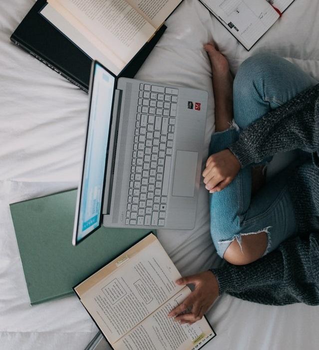 Jeune étudiant en jean qui travaille sur son lit