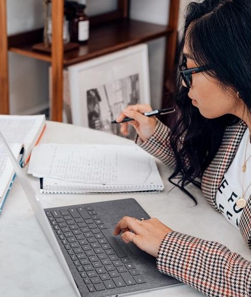 Etudiante qui révise ses cours entre carnet et PC
