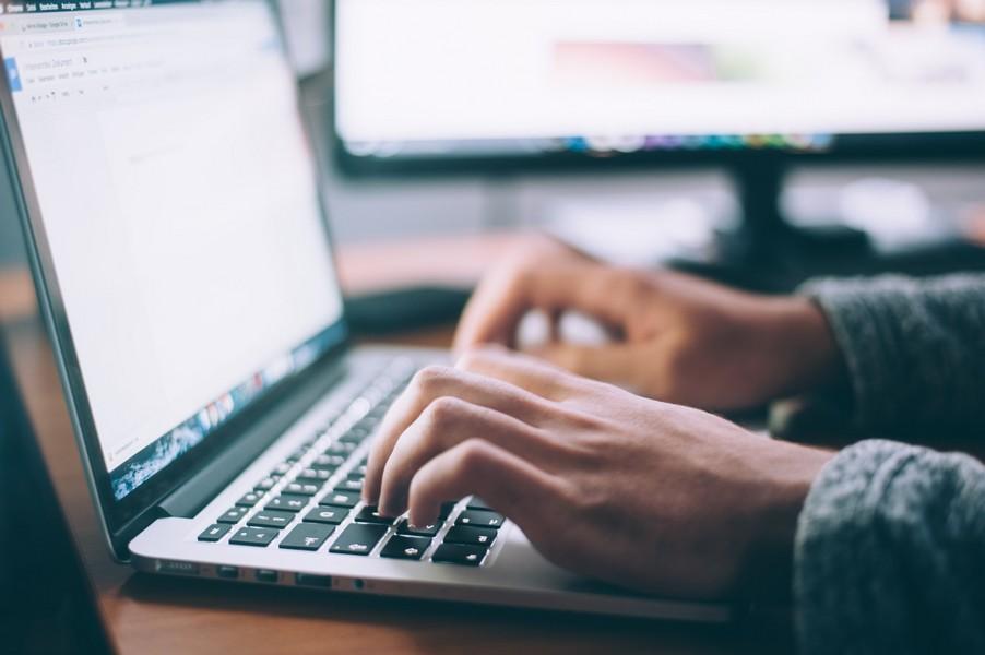 personne qui écrit sur le clavier de son ordinateur