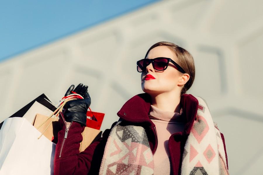 femme qui sort d'une session shopping avec des sacs de magasins de prêt-à-porter
