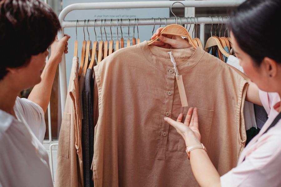 vendeuse de vêtements qui montre une blouse à une cliente