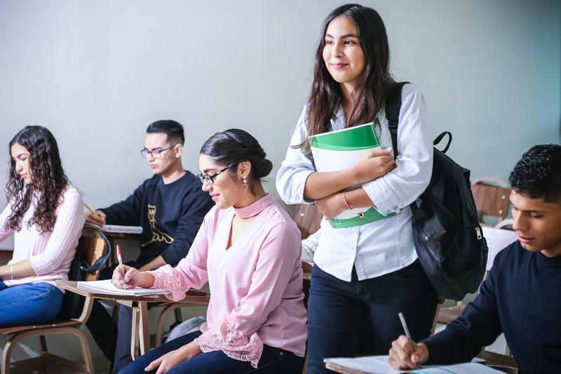 femme qui se lève de sa place en classe avec un classeur dans les mains